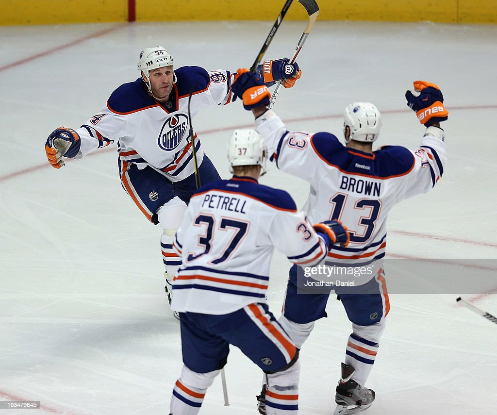 Ryan Smyth #94, Lennart Petrell #37 and Mike Brown #13 of the Edmonton Oilers celebrate a goal against the Chicago Blackhawks at the United Center on March 10, 2013 in Chicago, Illinois.