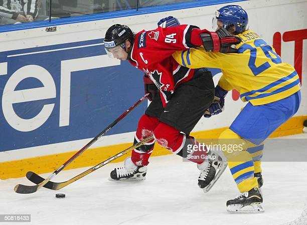 Ryan Smyth of Canada fights for the puck with Samuel Palsson of Sweden in the teams' match at the International Ice Hockey Federation World...
