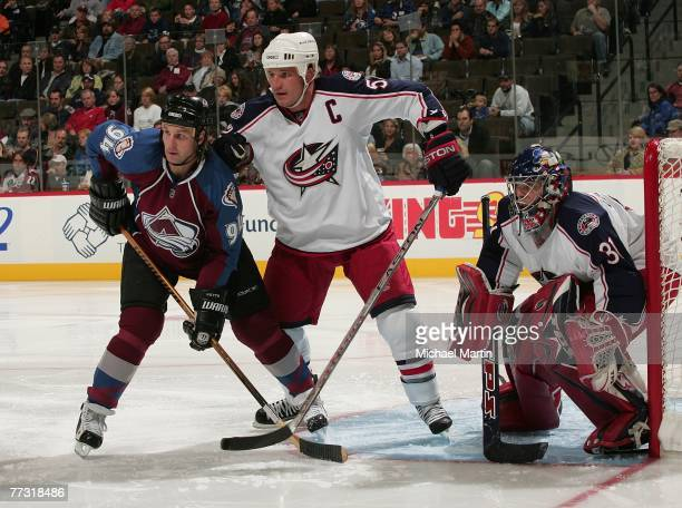 Ryan Smyth of the Colorado Avalanche is defended by Adam Foote and goalie Pascal Leclaire of the Columbus Blue Jackets at the Pepsi Center on October...