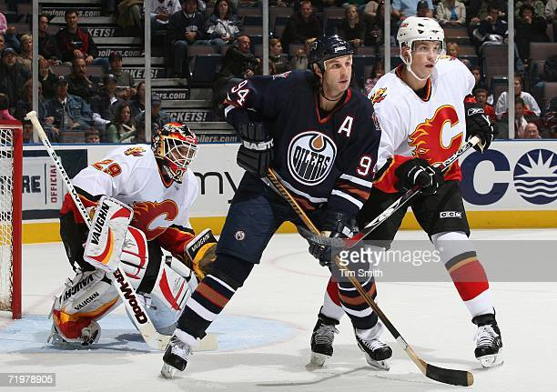 Ryan Smyth of the Edmonton Oilers tries to block goalie Jamie McLennan of the Calgary Flames as Brad Ference of the Flames watches the puck during...