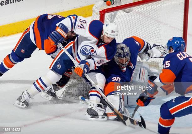 Ryan Smyth of the Edmonton Oilers tries to move the puck past goaltender Evgeni Nabokov of the New York Islanders at the Nassau Veterans Memorial...
