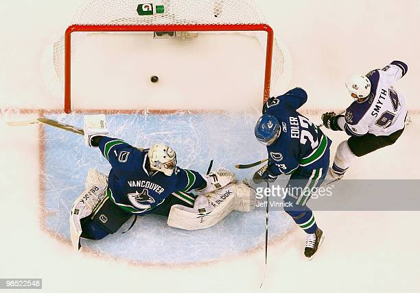 Ryan Smyth of the Los Angeles Kings and Alexander Edler of the Vancouver Canucks look on as the shot of Wayne Simmonds of the Los Angeles Kings gets...