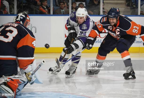 Ryan Smythe of the Los Angeles Kings is stopped by Martin Biron and Doug Weight of the New York Islanders at the Nassau Coliseum on October 12 2009...