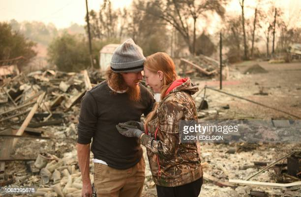 Ryan Spainhower and his wife Kimberly weep after finding a coin they had made during their honeymoon amidst the burned ashes of their home in...