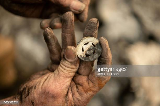 Ryan Spainhower displays a coin from his honeymoon that he found amidst the burned ashes of his home in Paradise California on November 18 2018