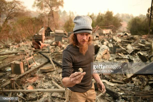 Ryan Spainhower displays a coin memento from his honeymoon that he found amidst the burned remains of his home in Paradise California on November 18...