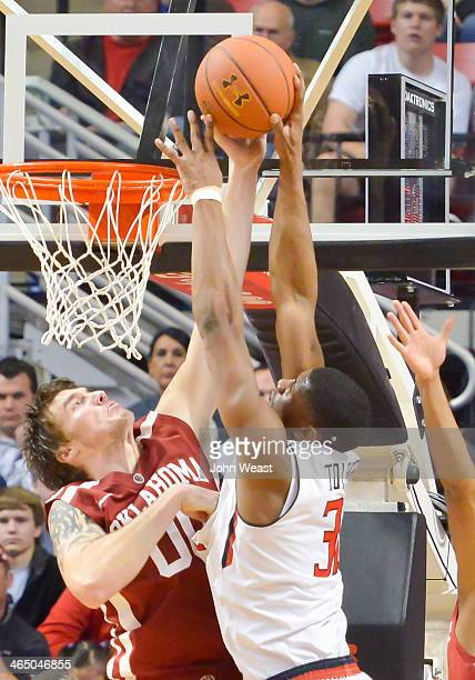 Ryan Spangler of the Oklahoma Sooners blocks an attempted dunk by Jordan Tolbert of the Texas Tech Red Raiders during game action on January 25 2014...