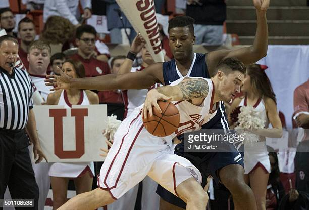 Ryan Spangler of the Oklahoma Sooners drives around Brandon Conley of the Oral Roberts Golden Eagles during the first half of NCAA college basketball...