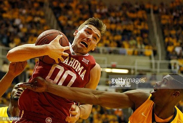 Ryan Spangler of the Oklahoma Sooners pulls down a rebound during the game against Jonathan Holton of the West Virginia Mountaineers at the WVU...
