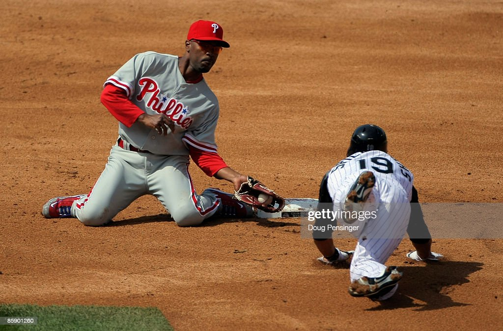 Ryan Spilborghs #19 of the Colorado Rockies is caught trying to steal second base and is tagged out by Shortstop Jimmy Rollins #11 of the Philadelphia Phillies during MLB action on Opening Day at Coors Field on April 10, 2009 in Denver, Colorado.