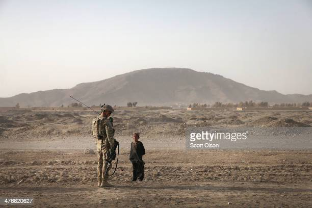 Ryan SpinuzziNichols from Reno Nevada with the US Army's 4th squadron 2d Cavalry Regiment patrols through a village on March 3 2014 near Kandahar...