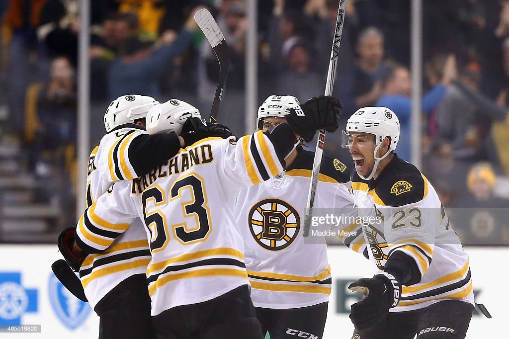 Ryan Spooner #51, Chris Kelly #23 and Maxime Talbot #25 congratulate Brad Marchand #63 of the Boston Bruins after he scored the game winning goal in overtime against the Philadelphia Flyers at TD Garden on March 7, 2015 in Boston, Massachusetts. The Bruins defeat the Flyers 3-2 in overtime.
