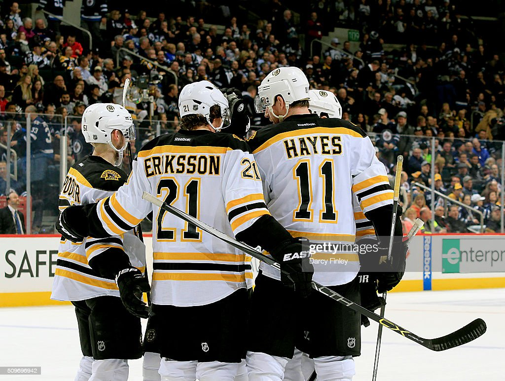 Ryan Spooner #51, Loui Eriksson #21 and Jimmy Hayes #11 of the Boston Bruins celebrate a third period goal against the Winnipeg Jets with teammates at the MTS Centre on February 11, 2016 in Winnipeg, Manitoba, Canada.