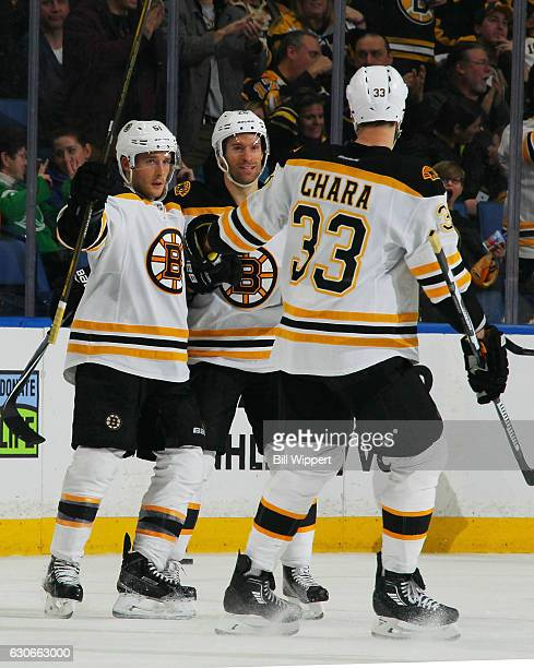 Ryan Spooner of the Boston Bruins celebrates his third period emptynet goal with Dominic Moore and Zdeno Chara against the Buffalo Sabres during an...