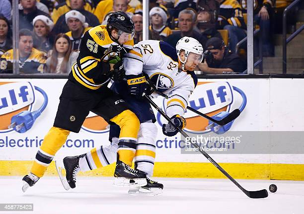 Ryan Spooner of the Boston Bruins hits Alexander Sulzer of the Buffalo Sabres in the first period during the game at TD Garden on December 21 2013 in...