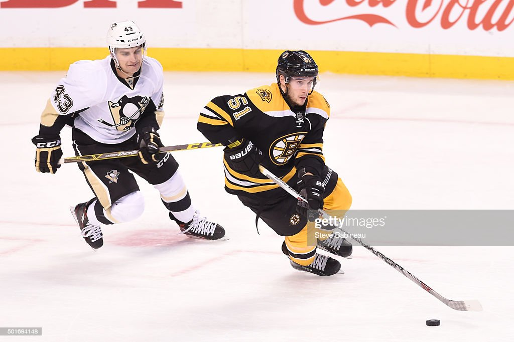 Ryan Spooner #51 of the Boston Bruins skates with the puck against Conor Sheary #43 of the Pittsburgh Penguins at the TD Garden on December 16, 2015 in Boston, Massachusetts.