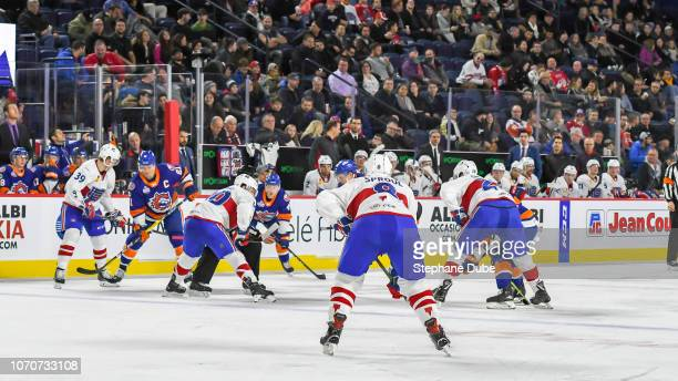 Ryan Sproul of the Laval Rocket waiting for the puck to drop with Jake Evans of the Laval Rocket at the faceoff circle and Hunter Shinkaruk of the...