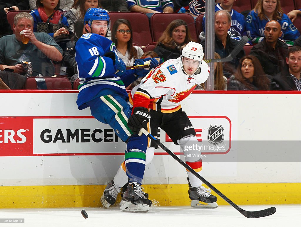 Ryan Stanton #18 of the Vancouver Canucks and Paul Byron #32 of the Calgary Flames battle along the boards for a loose puck during their NHL game at Rogers Arena January 10, 2015 in Vancouver, British Columbia, Canada. Calgary won 1-0.