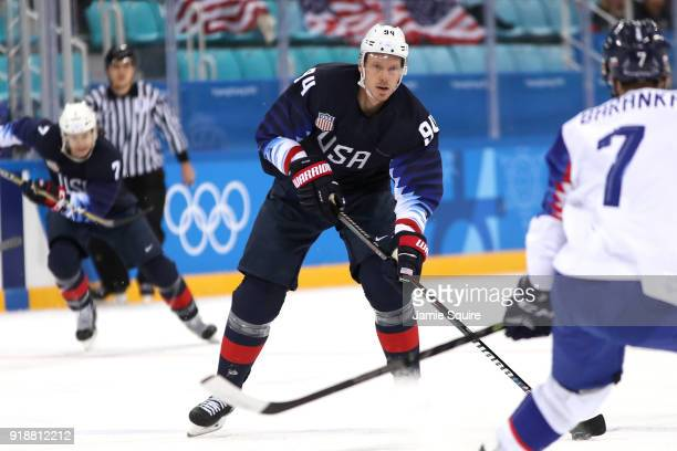 Ryan Stoa of the United States handles the puck against Ivan Baranka of Slovakia during the Men's Ice Hockey Preliminary Round Group B game at...