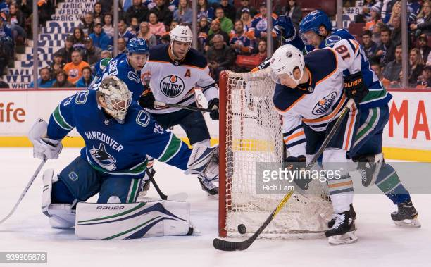 Ryan Strome of the Edmonton Oilers tries to get a stick on the loose puck while being checked by Alexander Edler of the Vancouver Canucks in NHL...