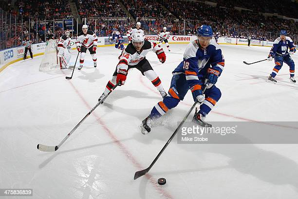 Ryan Strome of the New York Islanders skates with the puck as Adam Henrique of the New Jersey Devils pursues him at Nassau Veterans Memorial Coliseum...