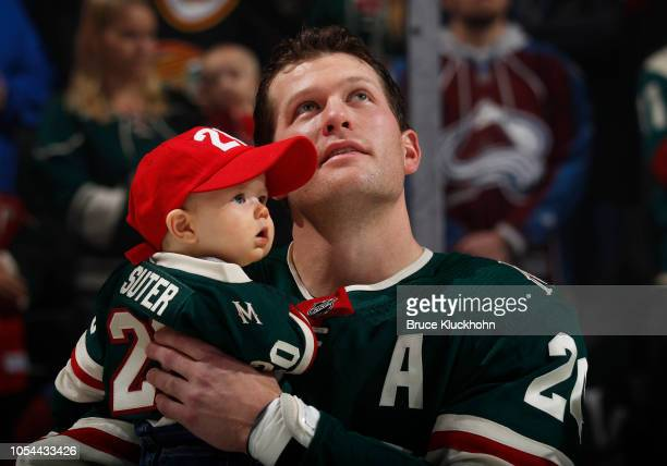 Ryan Suter of the Minnesota Wild holds his son as he watches a video honoring his 1000th career game in the NHL before a game between the Minnesota...