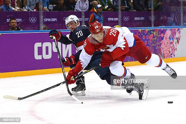 Ryan Suter of the United States and Alexander Syomin of Russia fight for the puck during the Men's Ice Hockey Preliminary Round Group A game on day...