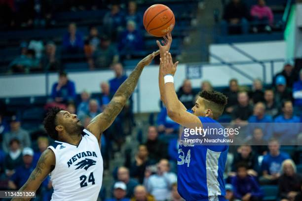 Ryan Swan of the Air Force Falcons attempts a three point basket over Jordan Caroline of the Nevada Wolf Pack during the second half at Clune Arena...