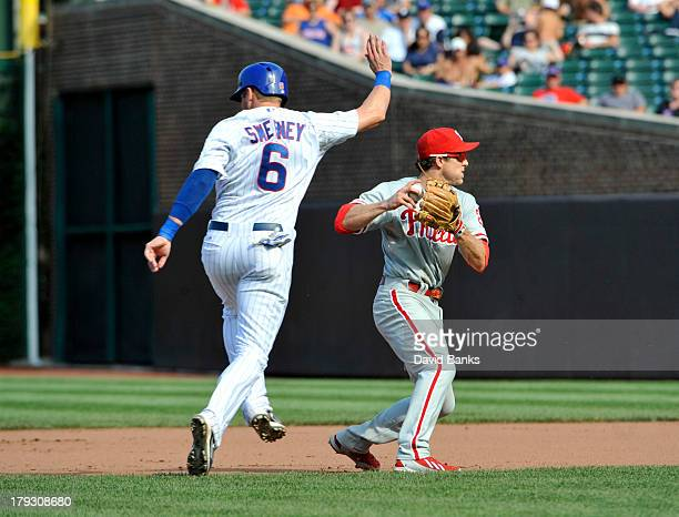 Ryan Sweeney of the Chicago Cubs avoids being tagged by Chase Utley of the Philadelphia Phillies during the eighth inning on September 1 2013 at...