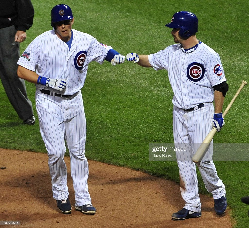 Ryan Sweeney #6 of the Chicago Cubs is greeted by Travis Wood #37 after scoring against the Colorado Rockies during the fifth inning on July 30, 2014 at Wrigley Field in Chicago, Illinois.