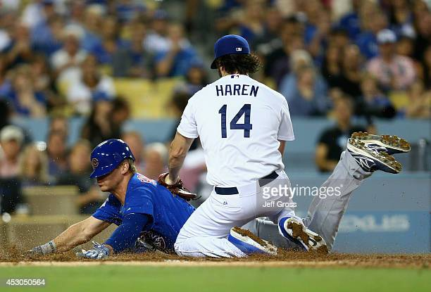 Ryan Sweeney of the Chicago Cubs slides past pitcher Dan Haren of the Los Angeles Dodgers on a wild pitch and scores a run in the third inning at...