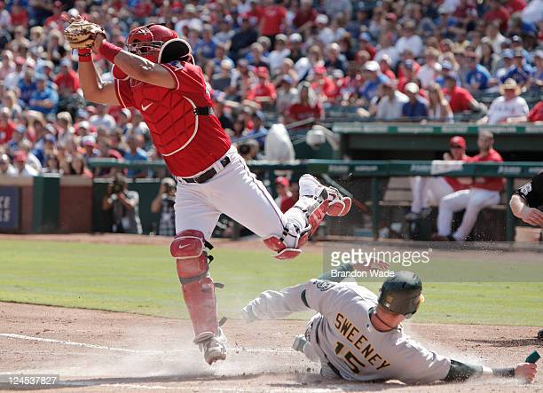 Ryan Sweeney of the Oakland Athletics scores a run on his teammates Kurt Suzuki not pictured RBI as Yorvit Torrealba of the Texas Rangers catches the...