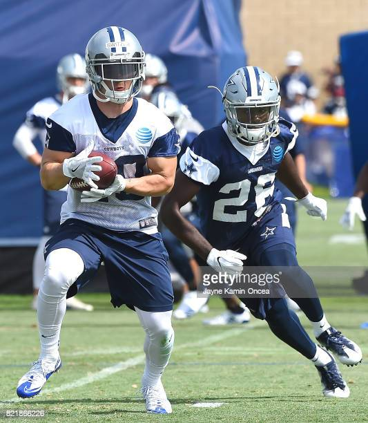 Ryan Switzer of the Dallas Cowboys catches a pass in front of Jameill Showers during training camp on July 24 2017 in Oxnard California
