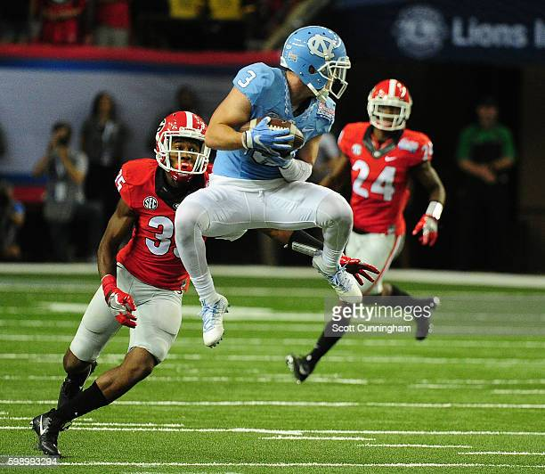 Ryan Switzer of the North Carolina Tar Heels makes a catch in front of Aaron Davis of the Georgia Bulldogs at the Georgia Dome on September 3 2016 in...