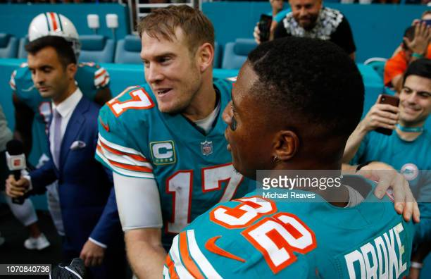 Ryan Tannehill and Kenyan Drake of the Miami Dolphins celebrate after defeating the New England Patriots 3433 at Hard Rock Stadium on December 9 2018...
