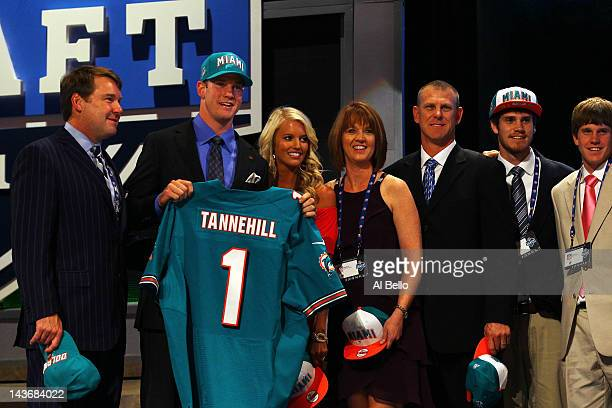 Ryan Tannehill from Texas AM holds up a jersey as he stands on stage with family and friends including his wife Lauren after he was selected overall...