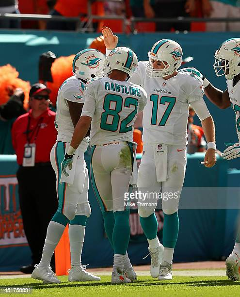 Ryan Tannehill of the Miami Dolphins congratulates Mike Wallace on a touchdown during a game against the Carolina Panthers at Sun Life Stadium on...