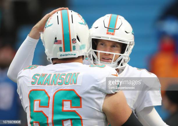 Ryan Tannehill of the Miami Dolphins embraces Travis Swanson as they warm up before the start of their NFL game against the Buffalo Bills at New Era...