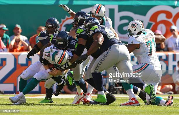 Ryan Tannehill of the Miami Dolphins is sacked by Chris Clemons of the Seattle Seahawks during a game at Sun Life Stadium on November 25 2012 in...