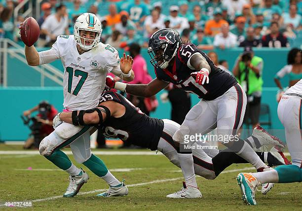 Ryan Tannehill of the Miami Dolphins is sacked by JJ Watt of the Houston Texans during a game at Sun Life Stadium on October 25 2015 in Miami Gardens...