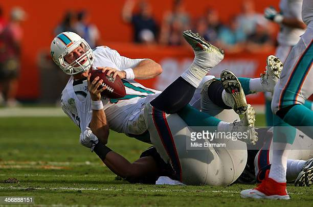 Ryan Tannehill of the Miami Dolphins is sacked by Sealver Siliga of the New England Patriots during a game at Sun Life Stadium on December 15 2013 in...