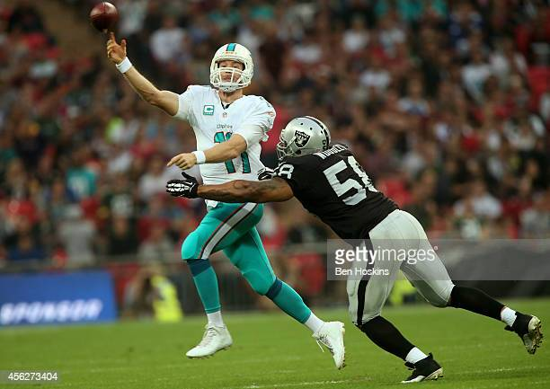 Ryan Tannehill of the Miami Dolphins passes as he is pressurised by LaMarr Woodley of the Oakland Raiders during the NFL match between the Oakland...