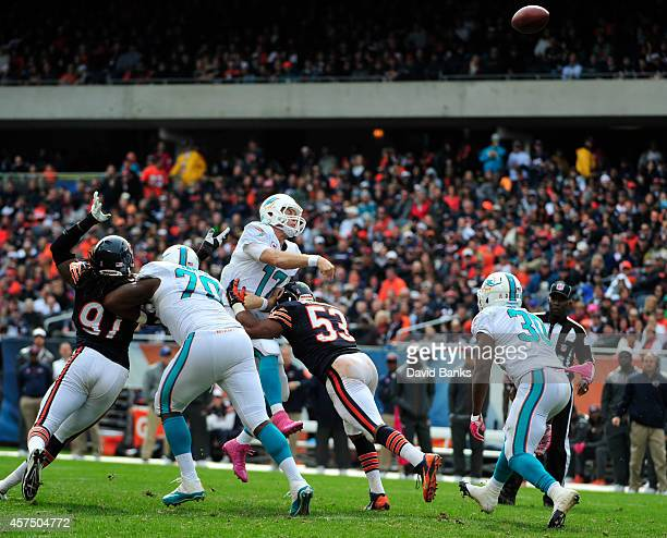 Ryan Tannehill of the Miami Dolphins passes as he's rushed by Darryl Sharpton of the Chicago Bears during the fourth quarter on October 19 2014 at...