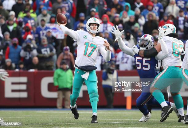 Ryan Tannehill of the Miami Dolphins throws the ball in the fourth quarter during NFL game action as Jerry Hughes of the Buffalo Bills tries to break...