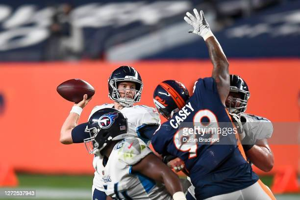 Ryan Tannehill of the Tennessee Titans passes as Jurrell Casey of the Denver Broncos reaches to block the pass in the third quarter of a game at...
