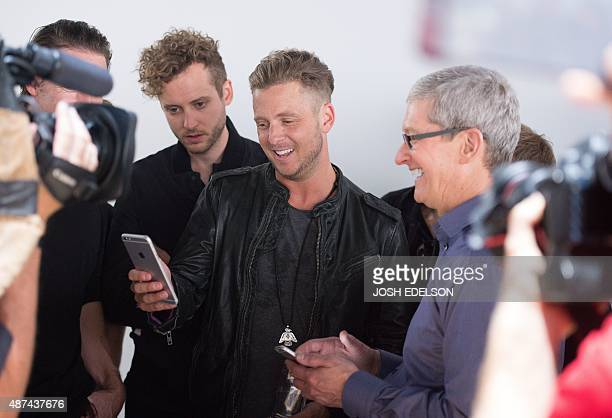 Ryan Tedder of OneRepublic views an iPhone 6s alongside Apple CEO Tim Cook during a media event in San Francisco California on September 9 2015 Apple...