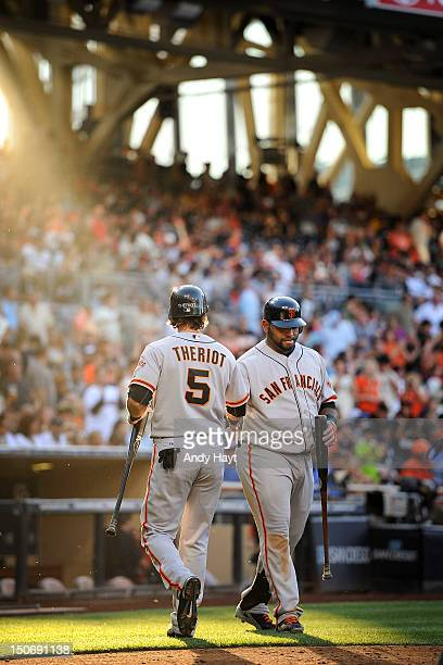Ryan Theriot is congratulated by Pablo Sandoval of the San Francisco Giants after scoring a run against the San Diego Padres at Petco Park on August...