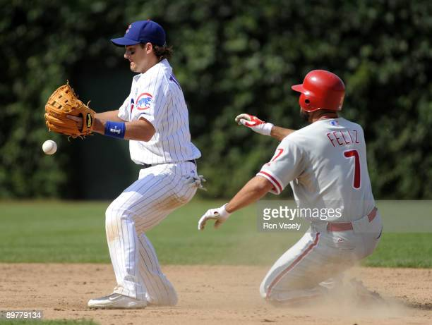 Ryan Theriot of the Chicago Cubs drops the ball as Pedro Feliz of the Philadelphia Phillies slides into second base during the game against the...