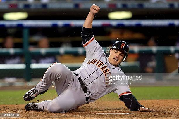 Ryan Theriot of the San Francisco Giants slides to home after a run off of Marco Scutaro of the San Francisco Giants an RBI single to center field...