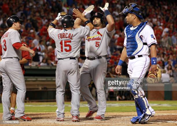 Ryan Theriot Rafael Furcal and Albert Pujols of the St Louis Cardinals celebrate after scoring on a Pujols threerun home run in the sixth inning...
